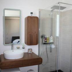 Plan en teck avec vasque à poser, armoire et douche avec paroi